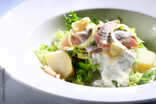 Fototapeta Sałatka  śledziowa. Śledź, śmietana, cebula i ziemniaki na zielonej sałacie. obraz