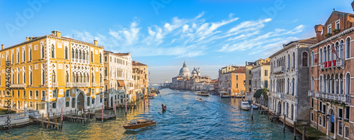 Papiers peints Bleu Grand Canal in Venice, Italy. Wide view of the main street panorama of the major street of Venice with motor boats with beautiful picturesque clouds in the sky. Basilica di Santa Maria della Salute.