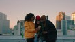 young african american woman taking photo of friends posing on rooftop at sunset enjoying hanging out together drinking alcohol sharing friendship in urban city skyline