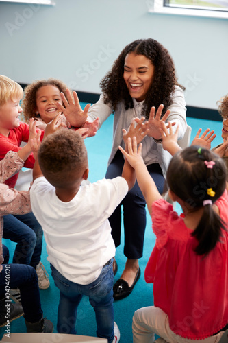 Fotografia Elevated view of infant school children in a circle in the classroom giving high
