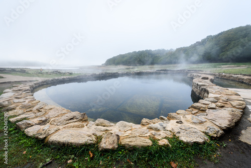 Natural Roman baths outdoors with hot steam and thermal water.