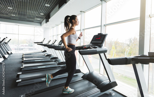 Fotografia Sports woman training on treadmill near the window