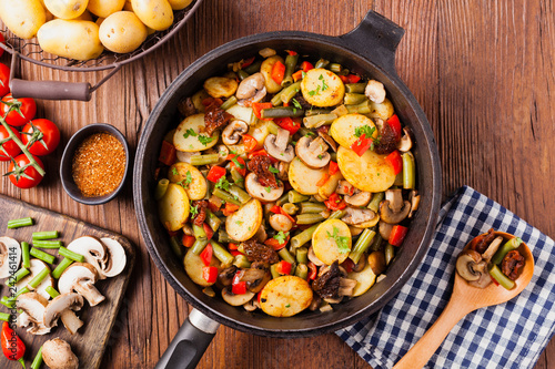 Fototapeta Fried pan vegetables, with mushrooms and dried tomatoes. Seasoned with a mix of herbs. obraz