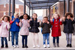 A group of smiling young multi-ethnic school kids wearing coats and carrying schoolbags standing in a row in walkway outside their infant school waving to camera, full length, front view
