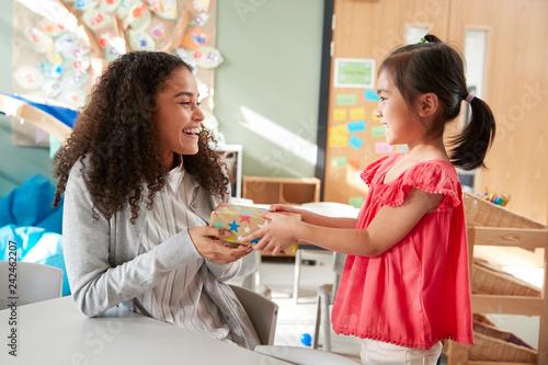Fotografia  Kindergarten schoolgirl giving a gift to her female teacher in a classroom, side