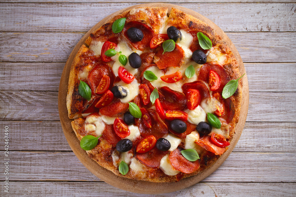 Pizza with pepperoni, tomatoes, cheese, olives and basil. Delicious pizza served on wooden plate on rustic background. overhead, horizontal