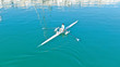 Aerial drone bird's eye view of sport canoe operated by young fit man in turquoise clear waters