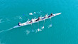 Aerial drone bird's eye view of sport canoe operated by team of young women in emerald clear sea Description96ult