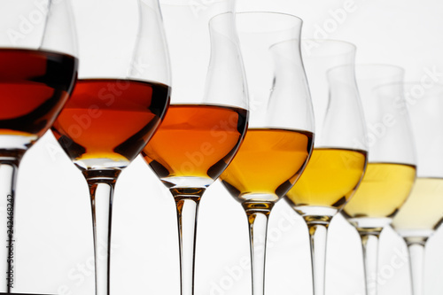 Fototapeta Row of cognac glasses with different stages of aging