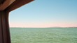 A boat sailing off and close to the coast of a harbor in the Ebro Delta region. The horizon is framed through an opening in the boat, and a slightly reddish sky is seen in a clear summer day.
