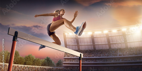 Fotografia, Obraz  Female Track and field athlete jumps over the barrier at the running track in pr