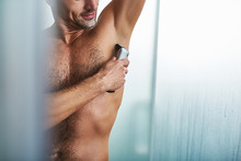 Young Man Carefully Shaving Armpit After Shower