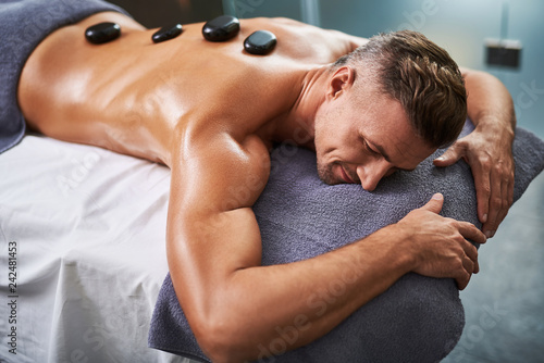 Young man lying on massage table while having spa treatment - 242481453