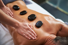 Young Man With Hot Mineral Stones On His Back Receiving Spa Treatment