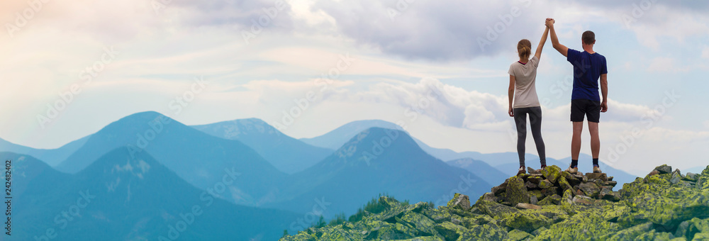 Fototapety, obrazy: Back view of young tourist couple, athletic man and slim girl standing with raised arms holding hands on rocky mountain top enjoying fantastic panorama. Tourism, traveling and climbing concept.