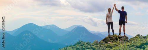 Back view of young tourist couple, athletic man and slim girl standing with raised arms holding hands on rocky mountain top enjoying fantastic panorama Wallpaper Mural