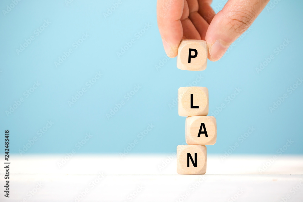 Fototapeta Hand hold wooden cube with PLAN word. The concept of planning in business.