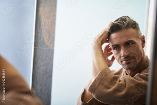 Fotografia  Handsome young man looking in the mirror at bathroom