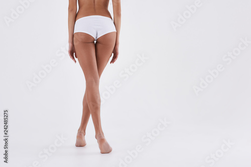 Valokuvatapetti Young lady demonstrating her slender legs and perfect buttocks