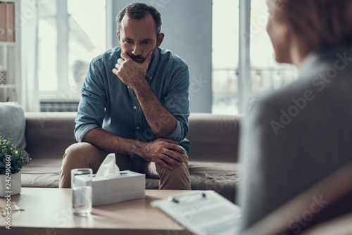 Photo Serious man frowning while sitting in front of the coffee table