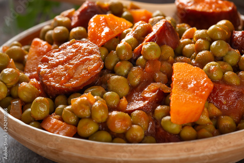 Peas stew with carrot and pork sausages in a traditional Romanian bowl