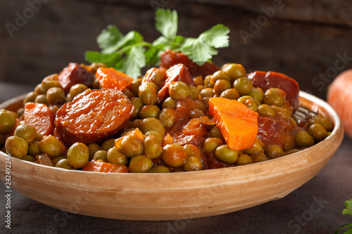 Peas stew with carrot and pork sausages