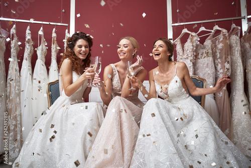 Fototapeta Full length of happy brides with champagne glasses