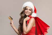 Portrait Of Attractive Cute Woman In Santa Hat Holding Shopping Bags And Credit Card. Gray Background.