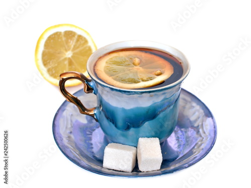 Fotografie, Obraz  Vintage elegant stylish graceful beautiful porcelain cup with golden handle and two pieces of sweet sugar on dish of morning tea with lemon on white background with half lemon