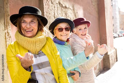 Tre amiche di età matura in viaggio con il cappellino fanno l'autostop sorridendo