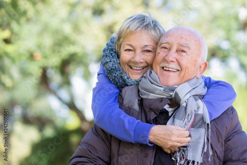 Obraz Coppia di anziani si abbraccia felici su sfondo parco  - fototapety do salonu