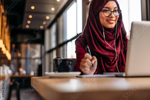 Fotografie, Tablou Female in hijab at cafe having video conference on her laptop
