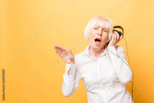 Foto  Elderly cheerful woman with headphones listening to music on a phone and dancing isolated on yellow background