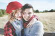 Romantic young couple of lovers look at the camera while smiling in love sitting in a outdoor wooden bench with nature as background