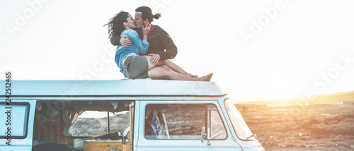Photo  Happy travel influencers couple kissing on minivan roof at sunset with desert on