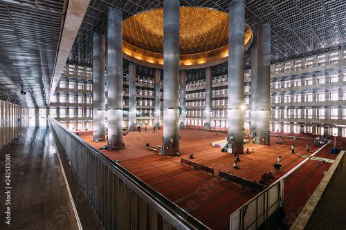 "Masjid Istiqlal Interior with prayers in Indonesia is the largest mosque in Southeast Asia. Named ""Istiqlal"", an Arabic word for ""independence"""