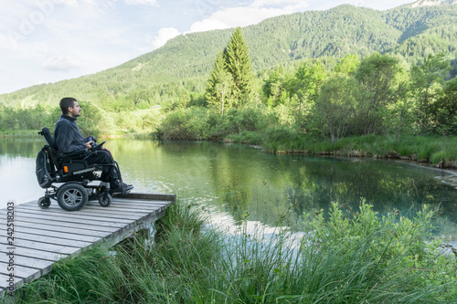 Disabled man on wheelchair enjoying and looking at beautiful nature on lake pier Fototapete