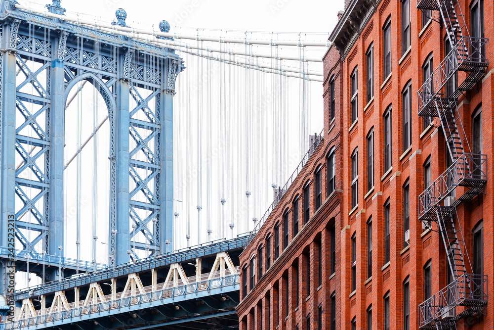 Bridge and brick industrial buildings. The famous suspension Manhattan Bridge photographed from DUMBO district in Brooklyn, New York City.