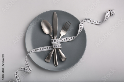 Plate and cutlery tied with measuring tape on grey background Canvas Print