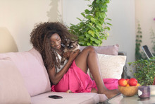 Beautiful African American, Black Young Woman With Crazy Curly Hair, Wearing A Bright Pink Pant Playing With Her Cat Outside In Her Patio On A Bright Sunny Day