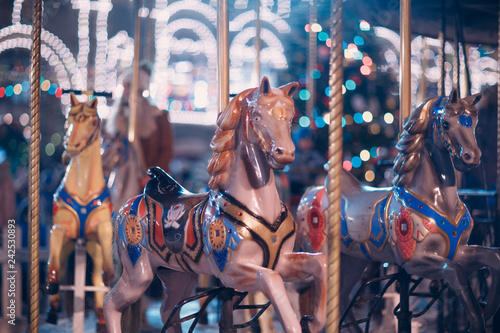 Fototapeta  A young woman rides a merry-go-round with horses at the New Year's Fair