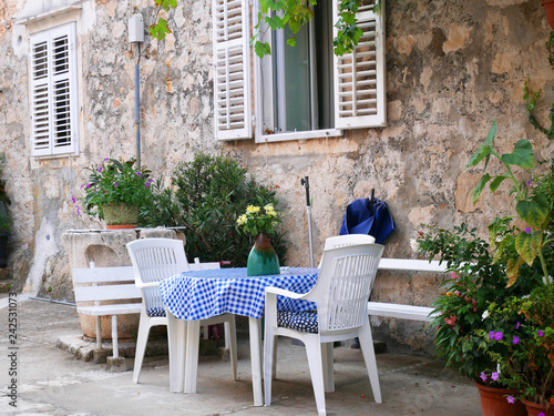 Poster Garden Tables and chairs of outdoor cafe in Croatia, Dubrovnik. Beautiful empty cafe with served tables