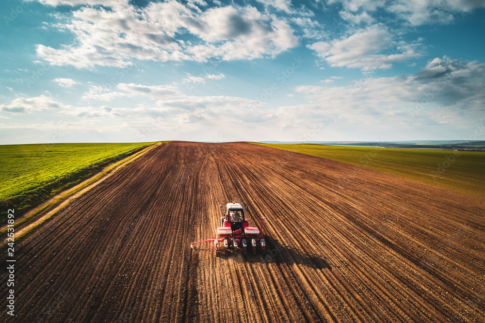 Fototapeta Farmer with tractor seeding crops at field, aerial view