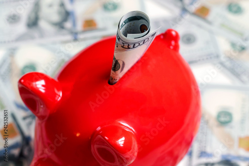 Fotografía  Red piggy bank and one hundred dollars, new 100 US dollar 2013 edition banknotes