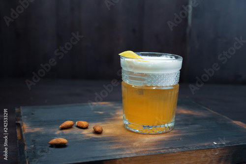 Foto op Plexiglas Cocktail Golden beer with white foam in a beer glass is standing on a black wooden table in the bar. The drink is decorated with peanuts. Served chilled. Enjoy the weekend