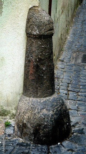 Road pillar in stone, with a phallic shape in a street of an Italian country Fototapet