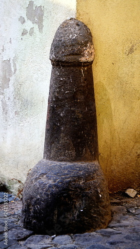Valokuva  Road pillar in stone, with a phallic shape in a street of an Italian country