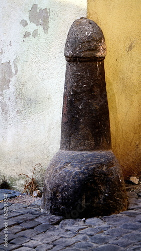 Road pillar in stone, with a phallic shape in a street of an Italian country Tablou Canvas