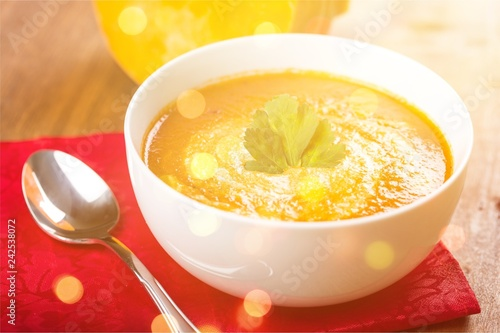 Tasty Pumpkin or carrot soup on background