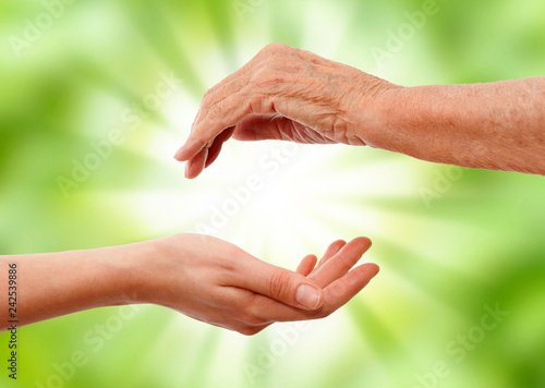 Stampa su Tela  young hand holding and elder one